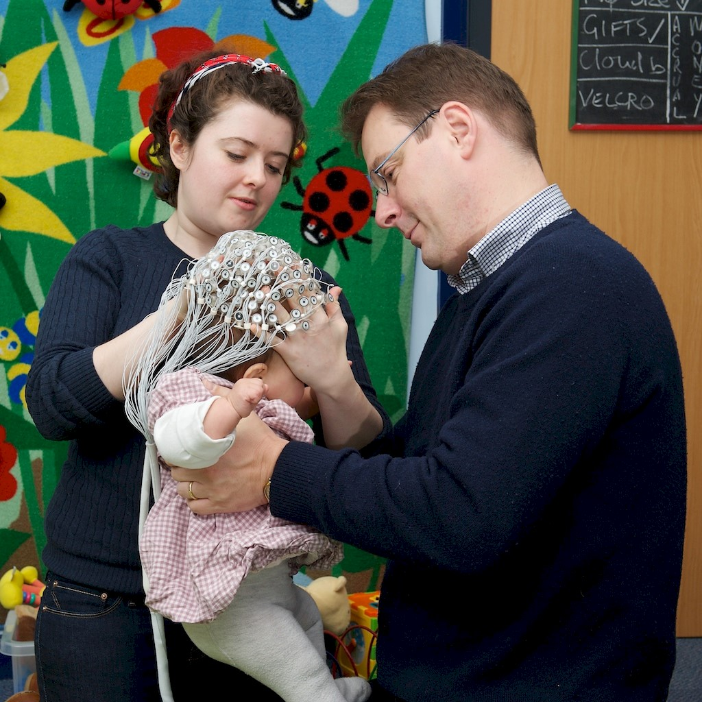 Researcher and parent putting electrode cap on baby
